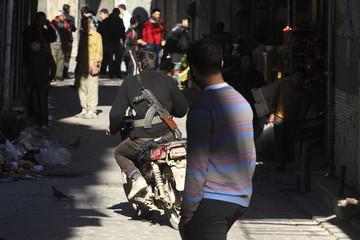 A member of the Free Syrian Army rides a motorcycle in the old city of Aleppo