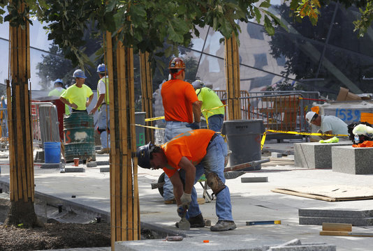Workers install stone and pavers on the main plaza area as work continues on the National September 11 Memorial and Museum at the World Trade Center site in New York
