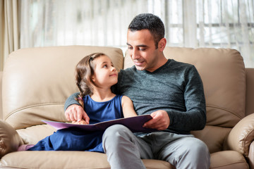 Happy Little Girl And Father Reading Book Together
