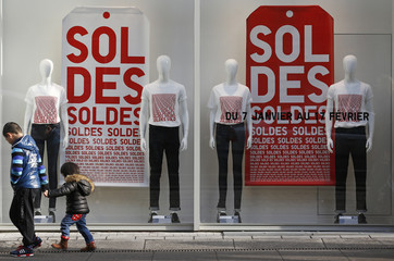 Children walk past a clothing store window with discount signs in Strasbourg, during the first day of winter sales in France