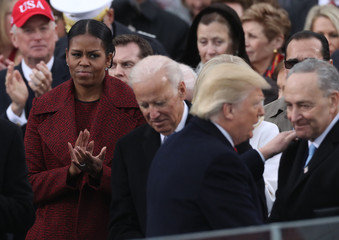Outgoing U.S. first lady Obama watches as incoming President Trump speaks with Senator Schumer during inauguration ceremonies for Trump at the U.S. Capitol in Washington