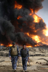 Iraqi security forces walk as fire and smoke rises from oil wells, set ablaze by Islamic State militants before fleeing the oil-producing region of Qayyara