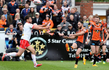 Luke Gale of Castleford Tigers in action with Jon Wilkin of St Helens