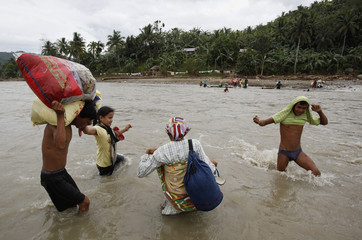 Typhoon Washi survivors wade in a river near a bridge destroyed by flash floods in Iligan city