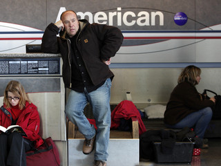 A passenger leans against an unoccupied ticket booth at JFK International Airport as he waits for the airport to reopen in New York