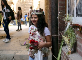 An Egyptian Coptic Christian girl carries flowers while wearing a palm decoration during Palm Sunday inside a Church in Old Cairo