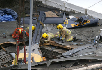 Rescue workers prepare to lift the wreckage of a police helicopter that crashed into a pub in central Glasgow