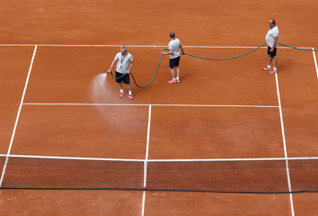 Workers spray water on the court at the French Open tennis tournament at the Roland Garros stadium in Paris