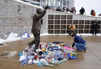 Laura Scott lays a flower at the base of the Joe Paterno statue at Penn State University in State College
