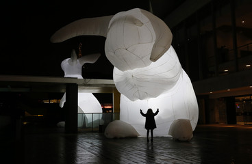 "A child looks at art installation ""Intrude"", featuring giant illuminated white rabbits, in central London"