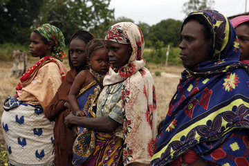 Women look on as residents talk to police officers after an attack in Panda Nguo, Lamu County