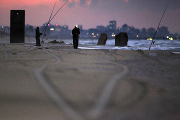 Part of the Gaza Strip is seen in the background as Israelis fish at Zikim beach, near Ashkelon