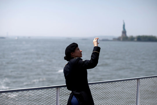 New U.S. citizen and U.S. Army Specialist Gabriella Calderon, originally from Honduras takes a photograph as she rides a ferry past the Statue of Liberty after naturalization ceremony at the Ellis Island Museum of Immigration in New York