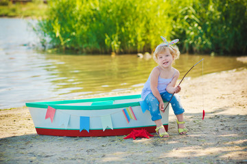 A cute little girl in a red bathing suit standing on the beach against the backdrop of boats