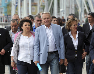 Aubry, the head of the French Socialist Party speaks with France's Prime Minister Ayrault, as they walk near the La Rochelle's Harbour, during the French Socialist Party in La Rochelle