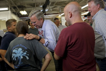 U.S. Republican presidential candidate Jeb Bush leans in to talk to employee Karina Rohrdanz after speaking at R.E. Prescott company in Exeter