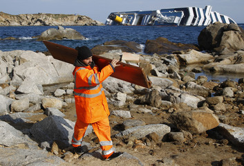 A worker carries a piece of debris from the Costa Concordia cruise ship ran that aground at Giglio island