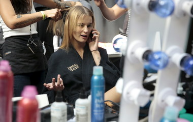 A model winks and talks on the phone while having her hair done before the presentation of the Holly Fulton Spring/Summer 2016 collection during London Fashion Week in London