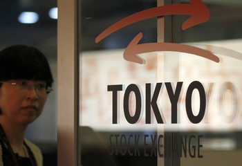 A woman walks past a logo of Tokyo Stock Exchange at the bourse in Tokyo