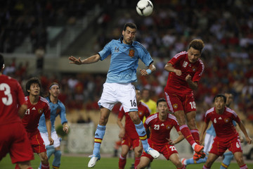 Busquets fights for the ball with Lin during their friendly soccer match leading up to Euro 2012 in Seville