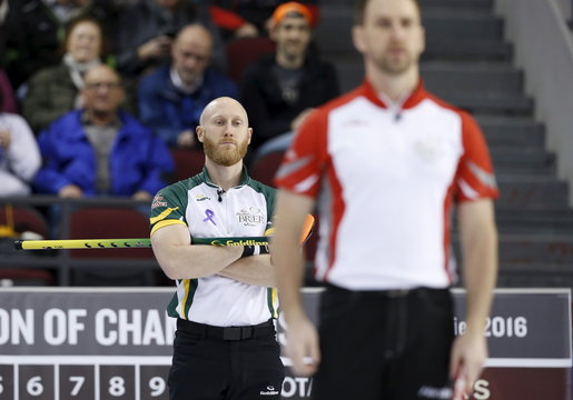 Team Northern Ontario skip Jacobs looks on as Team Newfoundland and Labrador skip Gushue lines up a shot during their page playoff game at the Brier curling championships in Ottawa
