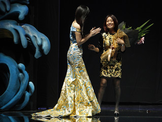 Chinese designer Guo Pei receives flowers at the end of her Asian Couture fashion show in Singapore