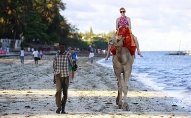 A tourist rides on a camel's back at the Jomo Kenyatta public beach in Mombasa