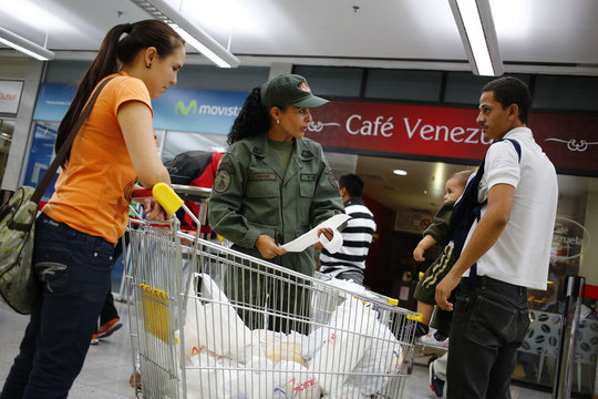 An army reservist checks a list of items purchase as people leave with their shopping at a state-run Bicentenario supermarket in Caracas