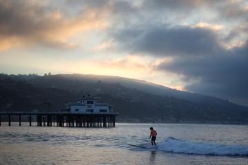 A surfer rides a wave in Malibu