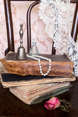 Old stuff on a shabby chair: books, photo, lace, silver handbell, pearl beads, perfume bottle