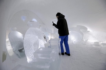 A man takes a picture of a room in the Ice hotel in Jukkasjarvi