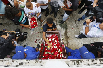 A kid lays flowers on the coffin of Wilton Esteves Domingos, one of five youths killed after being shot by police officers in Costa Barros neighborhood, during his burial in Rio de Janeiro