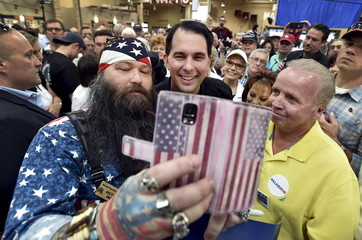 Republican presidential candidate and Wisconsin Governor Scott Walker takes a selfie with supporters during a visit at a Harley Davidson motorcycle dealership in Las Vegas