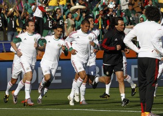 Players of the Mexican team warm up before their 2010 World Cup Group A soccer match against Uruguay at Royal Bafokeng stadium in Rustenburg