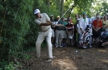 Mickelson of the U.S. hits his shot righthanded out of the bamboo trees on the fourth hole during final round play in the 2012 Masters Golf Tournament in Augusta