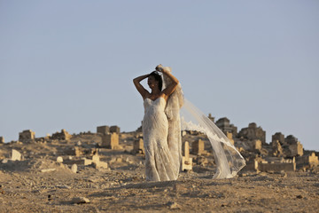 An Israeli bride poses for her wedding photographer as graves are seen in the background in Judean desert near Jericho