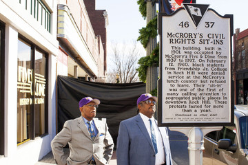 Massey and McCleod, members of the Friendship Nine, look at a historical commemorative marker outside the Five & Dine diner in Rock Hill