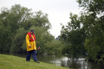Dike walker checks condition of dike that contains swelling Oder River near eastern German village of Ratzdorf