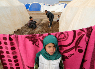 A displaced Iraqi girl, who fled the Islamic State stronghold of Mosul, stands at Khazer camp
