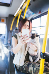 Beautiful young woman sitting in city bus with her pug and taking selfie photo. Selective focus on phone.