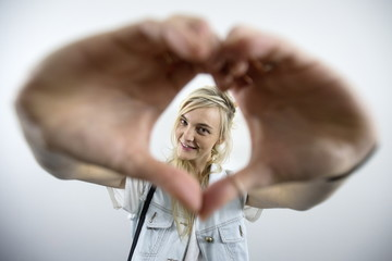 A model poses for a portrait while making a heart symbol with her hands backstage before the Michael Kors Spring/Summer 2016 collection presentation during New York Fashion Week in New York