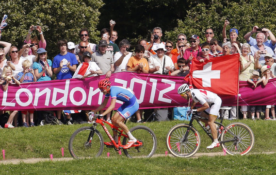 Czech Republic's Jaroslav Kulhavy (L) rides ahead of Switzerland's Nino Schurter as they approach the finish line during the last lap of the men's cross-country mountain bike event at Hadleigh Farm at the London 2012 Olympic Games