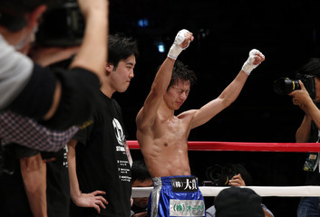 Challenger Taguchi of Japan rises his hands after the announcement of the winner during his WBA boxing lightfly weight title bout against Rossel of Peru in Tokyo