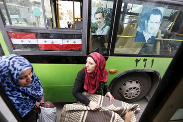 Women carry belongings they collected from their damaged houses as they get into into a bus after their visit to the city of Palmyra