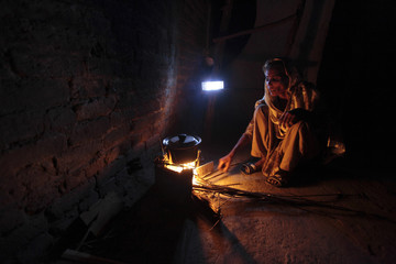 A woman cooks over a wood-burning fire under a battery-run emergency light during a power outage in a slum in Islamabad