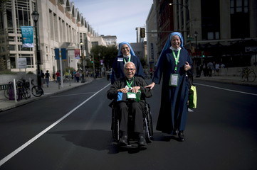 Rev. Richard Edward Jozwiak is pushed by Sisters of Our Mother of Divine Peace outside the World Meeting of Families