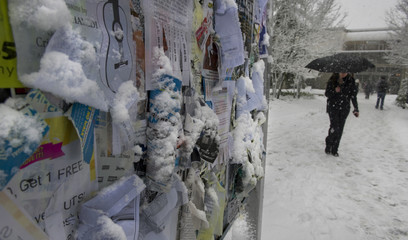 An outdoor message board is covered in snow from a winter storm at Simon University in Burnaby
