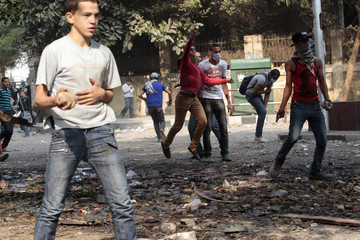 Anti-Mursi protesters throw stones during clashes with riot police at Tahrir Square in Cairo