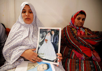 A pregnant Hamida Moussa poses with her wedding  photograph at refugee camp in Benghazi