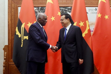 Angola's President Jose Eduardo dos Santos shakes hands with China's Premier Li Keqiang before their meeting at the Great Hall of the People in Beijing